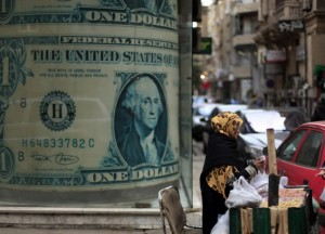 Big business: A vendor sells nuts in front of a giant poster of a U.S. dollar outside a currency exchange office in Cairo as the Government announced a £6,000 limit on how much can be taken out of the country.